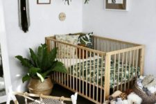 a tropical boho nursery with tropical bedding, baskets for storage, printed rugs, potted greenery
