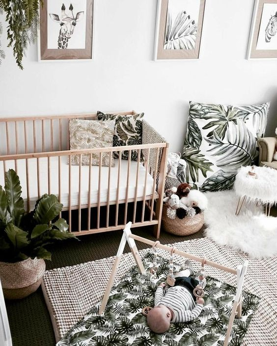 a tropical nursery done in neutrals, with tropical leaf prints and much potted greenery, a jute rug and a wooden crib