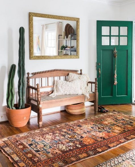 a vintage boho entryway with a vintage carved wooden bench, a boho rug, a potted cactus, a mirror in a gold ornate frame