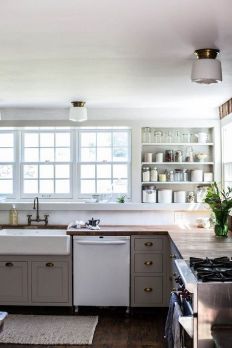 a vintage meets modern farmhouse kitchen with grey cabinets, butcherblock countertops, built-in shelves and a vitnage faucet
