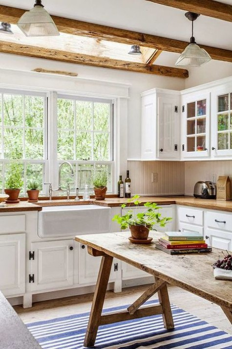 a welcoming farmhouse kitchen with wooden beams on the ceiling, a wooden table as a kitchen island and butcherblock countertops