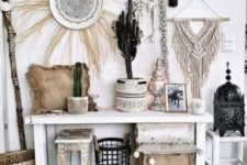a whimsical whitewashed boho entryway with macrame hangings, potted cacti, a decorative plate with grass, a console and some catchy stools and a boho rug