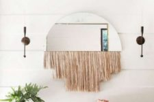 a whimsy boho entry with a woven bench, a basket for storage, a mirror with long fringe and a potted plant on a stand