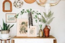 a whimsy boho entryway with decorative plates, a vintage console and potted greenery plus wicker touches