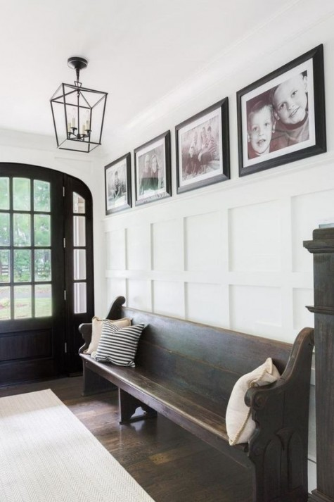 a white ceiling and wainscoting contrast a dark door, floor and furniture and make up a chic space