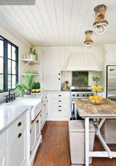 a white farmhouse kitchen with a stained floor, a vintage table, upholstered stools and touches of black