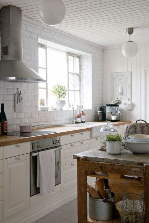 a white farmhouse kitchen with a white tile wall, vintage cabinets, a shabby chic table with a stone tabletop