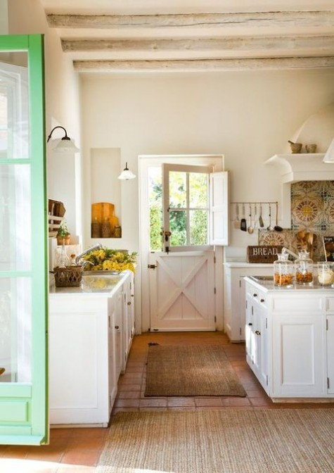 a white farmhouse kitchen with jute rugs, elegant white cabinets and natural wooden touches here and there