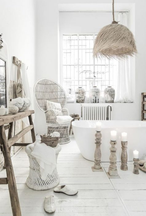 a whitewashed boho bathroom with an oval bathtub, a grassy lampshade, a peacock chair, wooden and rattan furniture and candles in wood candle holders