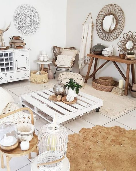 a whitewashed boho living room with shabby whitewashed furniture, jute and rattan items, baskets and candle lanterns