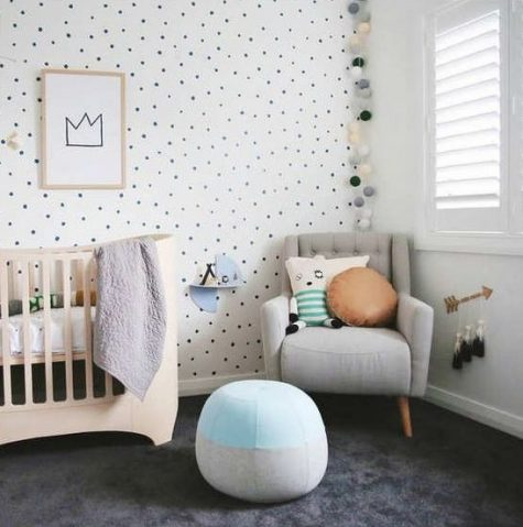 an adorable gender neutral nursery with a spotted wall, a whimsy crib, a light garland, pastel pillows and cushions