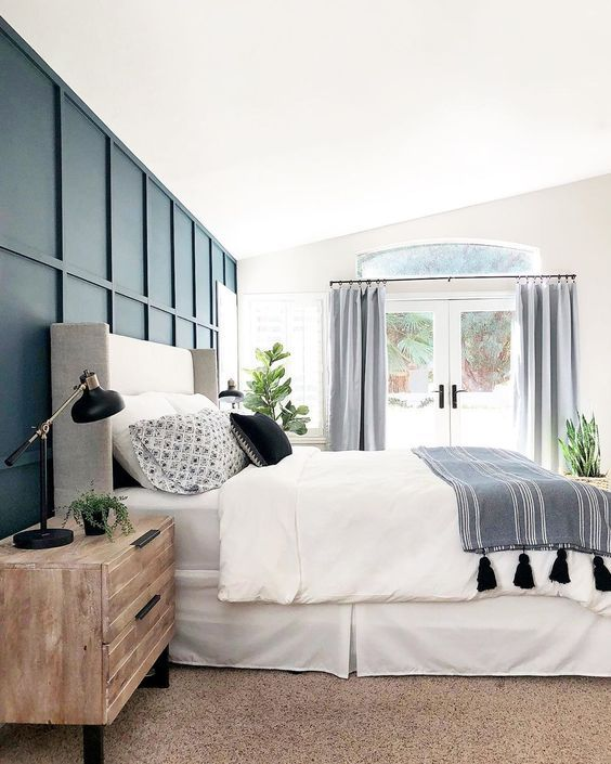 an airy and lively bedroom with a navy paneling accent wall that brings a bold and chic statement