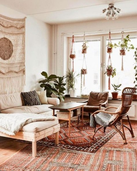 an elegant boho living room with rattan and wood furniture, boho rugs and pillows, planters in macrame hangers and a macrame hanging on the wall