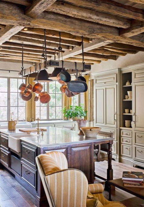 an elegant vintage farmhouse kitchen with neutral cabinets going up to the ceiling, a hanger for pans and a large kitchen island