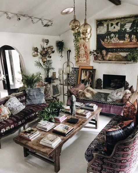 an epic gypsy living room with dark embroidered furniture, pendant lamps, a fireplace and boho pillows and artworks
