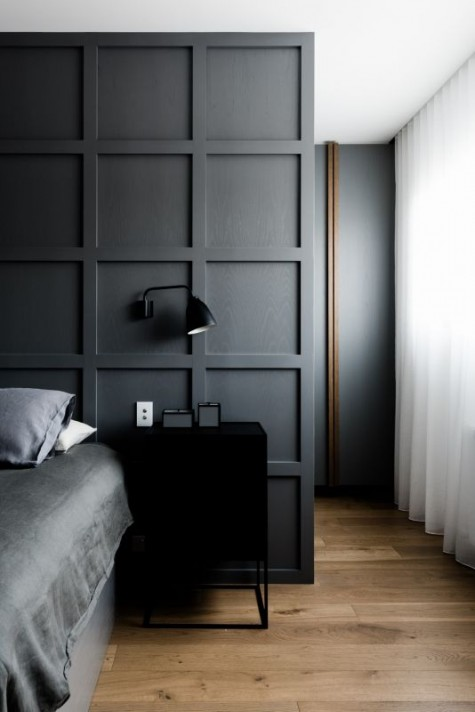 black paneling used as a headboard coming up to the ceiling and to divide the bedroom and the closet
