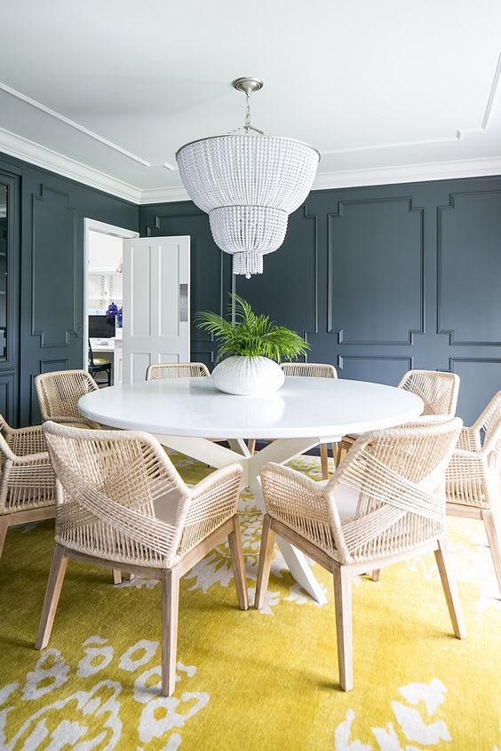 graphite grey paneling, rattan furniture, a white bead chandelier and a printed yellow rug for an eclectic dining room