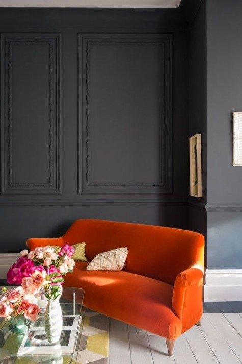 graphite grey wainscoting creates a moody ambience and a white floor and colorful furniture spruce it up