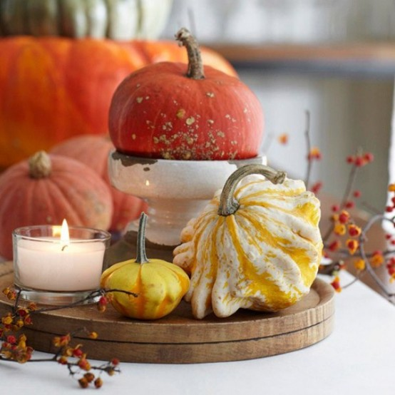 a bright fall centerpiece of a wooden tray, natural pumpkins, a candle and some dried berries