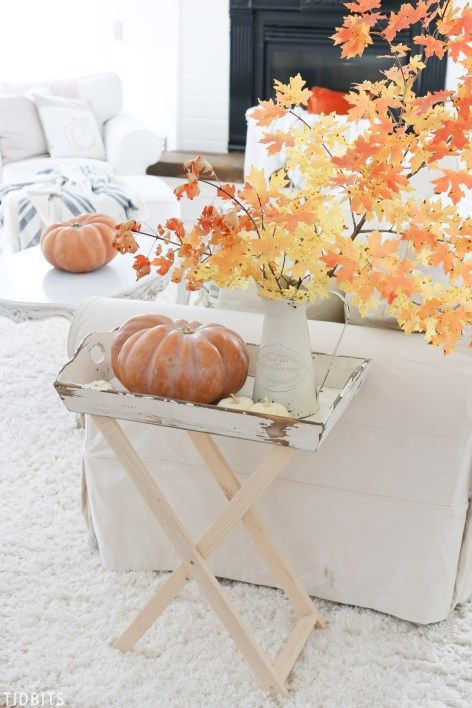 a bright fall leaf arrangement in a vintage whitewashed jug and a couple of heirloom pumpkins spruce up the neutral living room