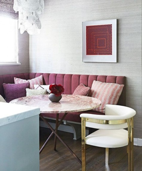 a burgundy upholstered bench and plum and pink pillows for a bold fall-infused eating space