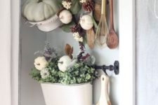 05 a colander with a green pumpkin, a wreath with leaves, pinecones and pumpkins and a pot with greenery and white pumpkins