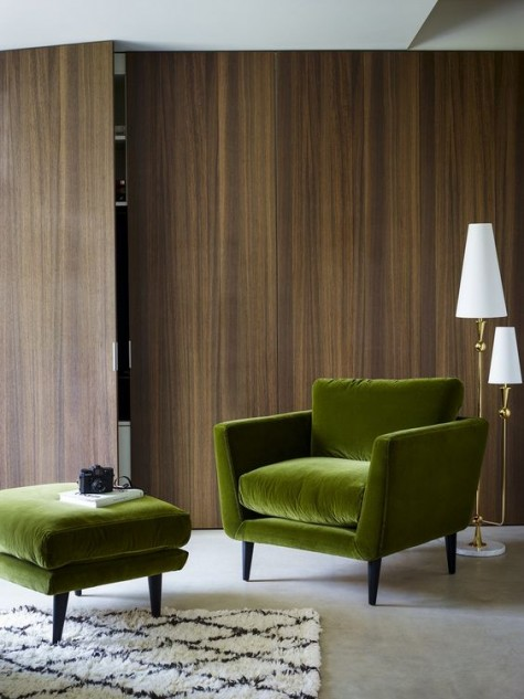 a green velvet chair and a footrest stand out in the backdrop of a plywood covered wall and make the space feel like fall