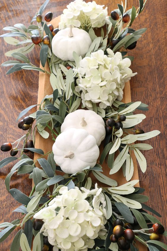 a cute natural fall centerpiece with foliage, white hydrangeas, foliage and olives for a harvest feel