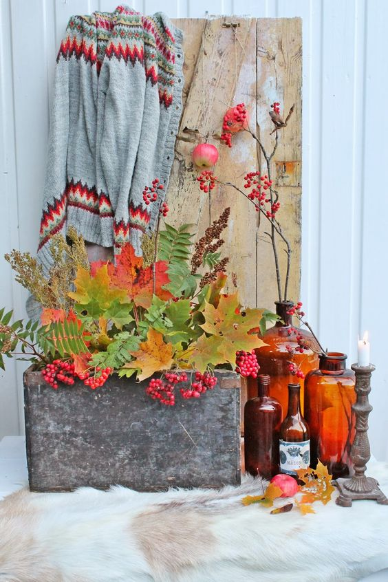 a stylish fall display with colorful bottles, candle holders, a concrete box with fall leaves and berries