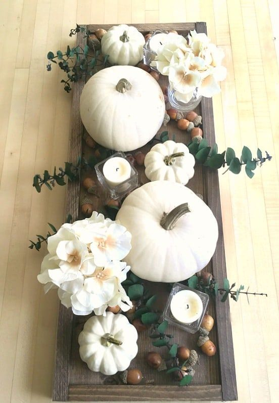 a dark stained wooden tray, white pumpkins, blooms, candles and acorns for a pretty fall centerpiece