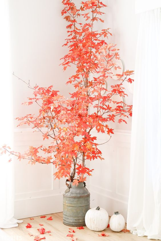 super bright red leaves on branches, a metal churn and some pumpkins will make a bold fall statement