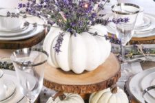 09 a fall centerpiece of white pumpkins, wood slices and lavender in a pumpkin vase