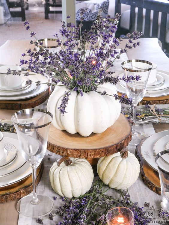 a fall centerpiece of white pumpkins, wood slices and lavender in a pumpkin vase