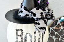 09 a white pumpkin with black studs, a black hat and a bat ribbon is a cool decoration or centerpiece for Halloween
