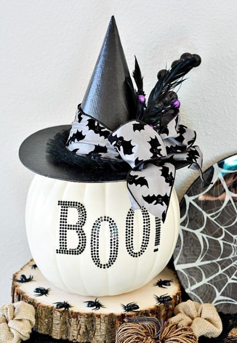 a white pumpkin with black studs, a black hat and a bat ribbon is a cool decoration or centerpiece for Halloween