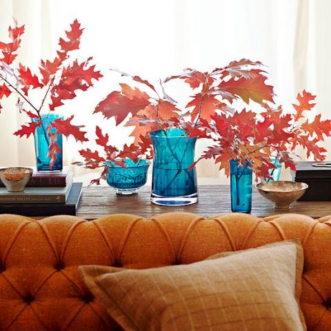 bright fall leaves arrangements in contrasting blue vases will make a bold statement in decor