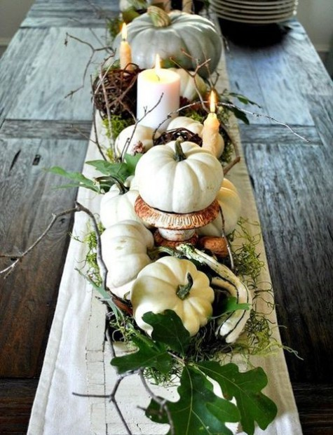 a gorgeous fall centerpiece using heirloom pumpkins, candles, driftwood, greenery, vine and foliage