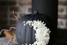 11 a matte black pumpkin with white flowers moon decor is a gorgeous idea for the coming Halloween