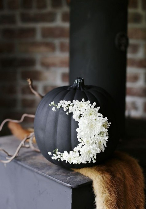 a matte black pumpkin with white flowers moon decor is a gorgeous idea for the coming Halloween