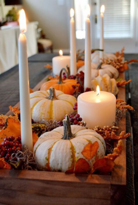 a pretty fall centerpiece of a wooden box, pumpkins, berries, bright foliage, moss, berries and candles