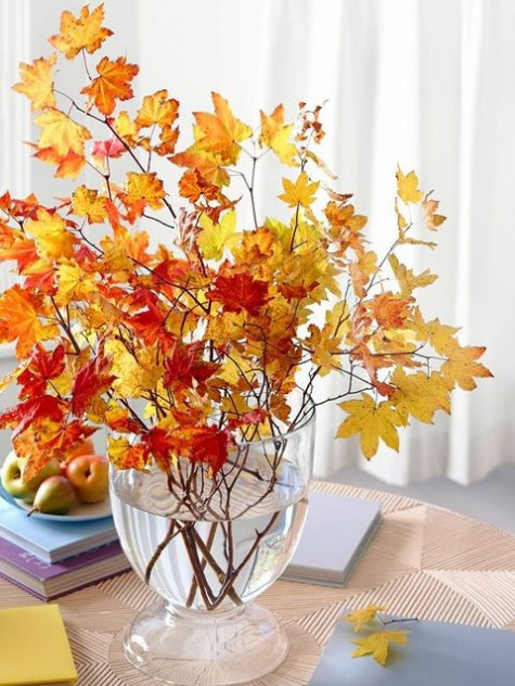 an oversized fall centerpiece with a large clear vase filled with branches with colorful fall leaves is amazing and easy to recreate