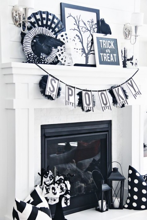 a black and white mantel with a banner, wreaths, signs, blackbirds, artworks and candle lanterns is a timeless option