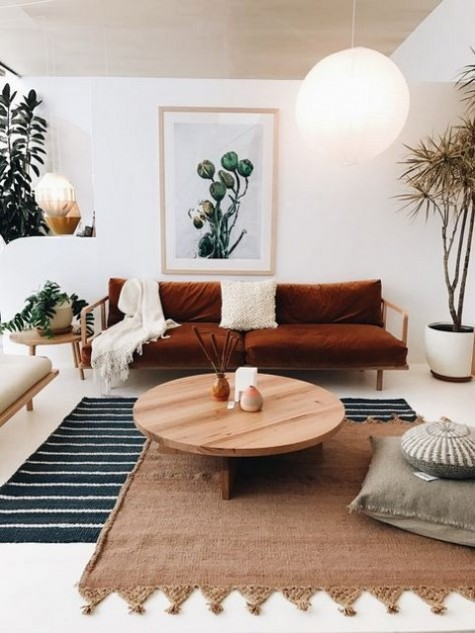 a rust-colored velvet sofa is a centerpiece of this boho living room and brings a fall feel here