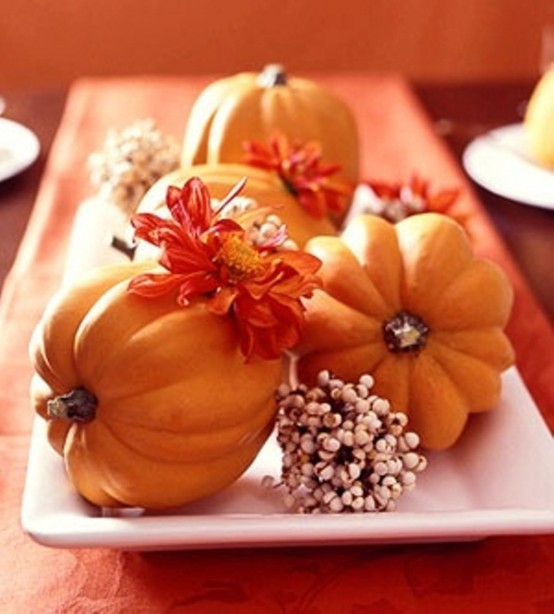 a rustic fall centerpiece of a white porcelain tray, berries, bright fall blooms and orange pumpkins