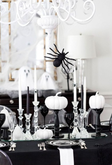 a black and white tablescape with black and sheer glasses, spiders, pumpkins and candles for Halloween
