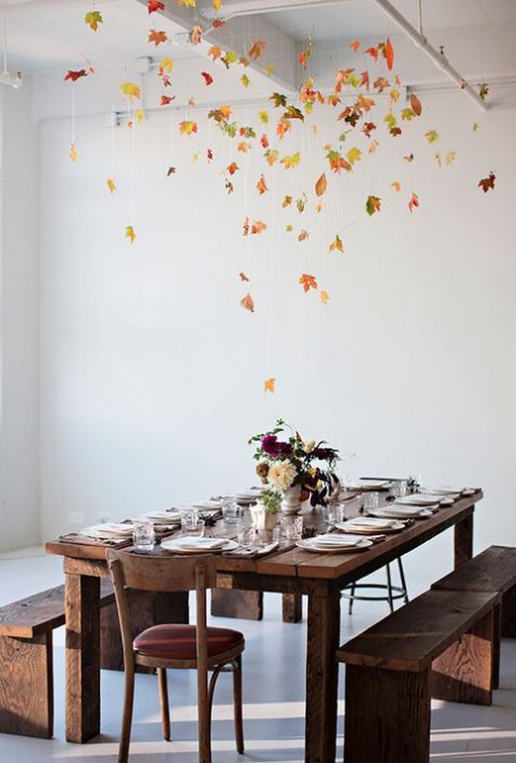 a gorgeous overhead fall leaf installation over the dining table is a very modern and bold idea