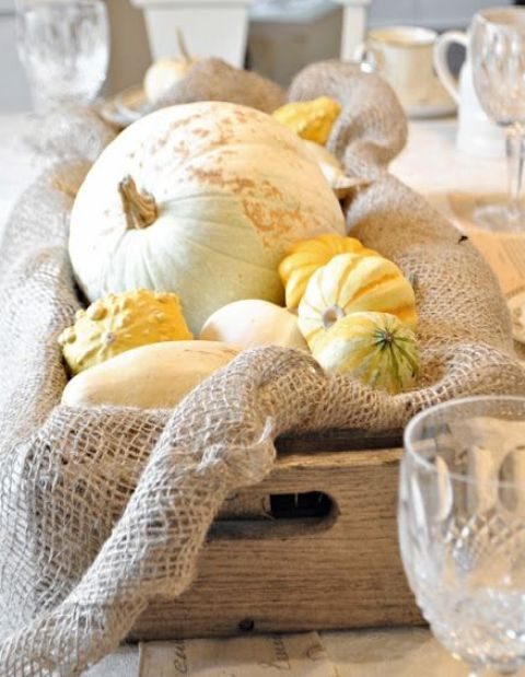 a rustic fall arrangement with pumpkins