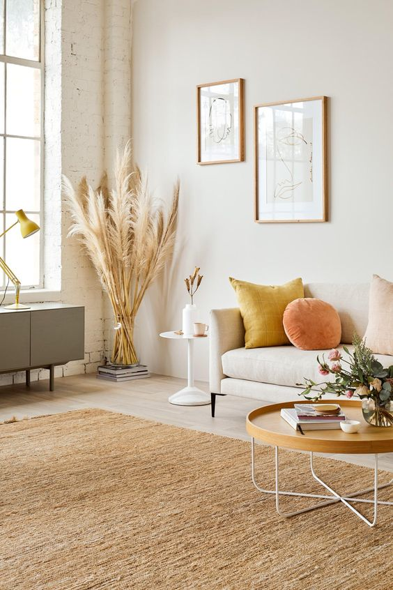 a bright and chic fall-inspired space done with orange and yellow touches, with a neutral rug and wheat
