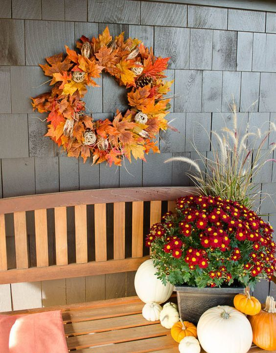 a bright fall leaf wreath with pinecones, yarn balls and twigs is a cool idea, and if it's faux   it's durable