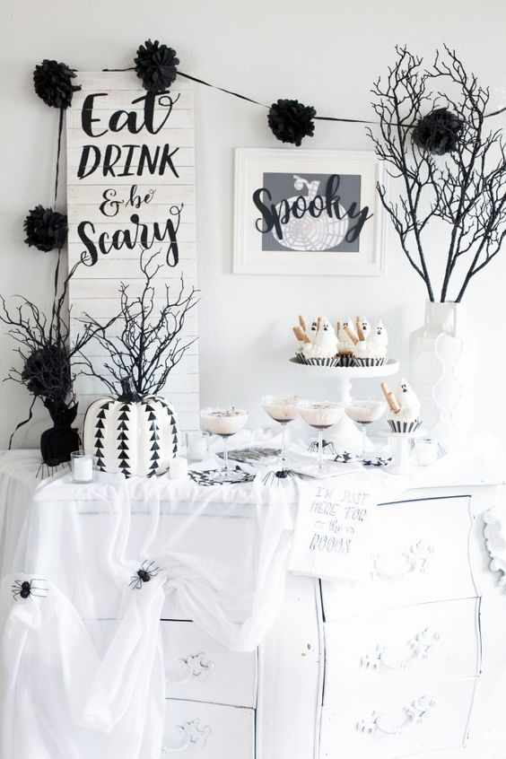a cool Halloween buffet table with ghost cupcakes, a stenciled pumpkin, black branches in a white vase, a couple of cool signs and spiderwebs